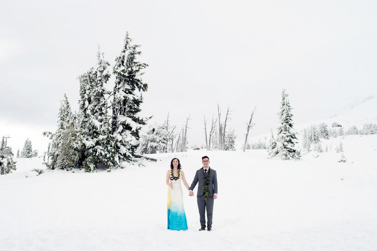 groom with bride wearing colorful dress in snow at timberline lodge