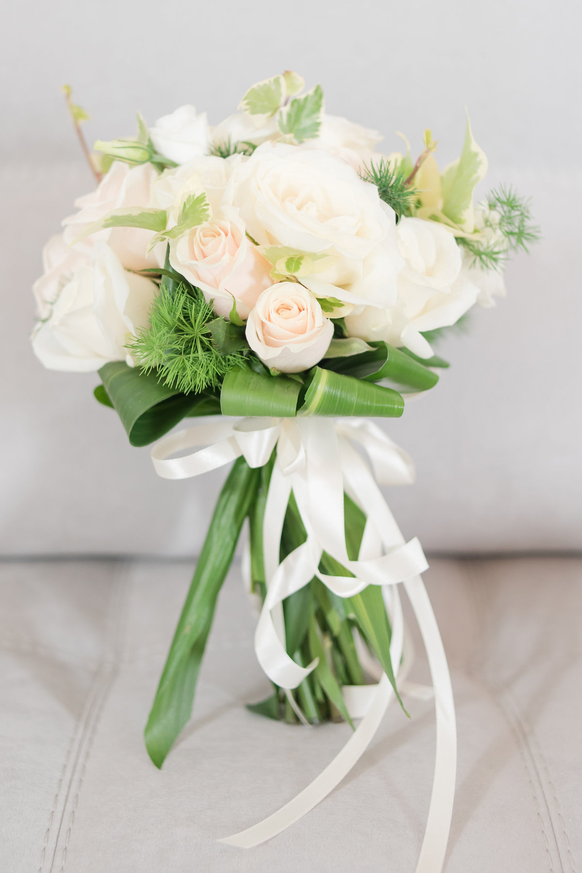 green and ivory bridal bouquet on grey couch in Italy