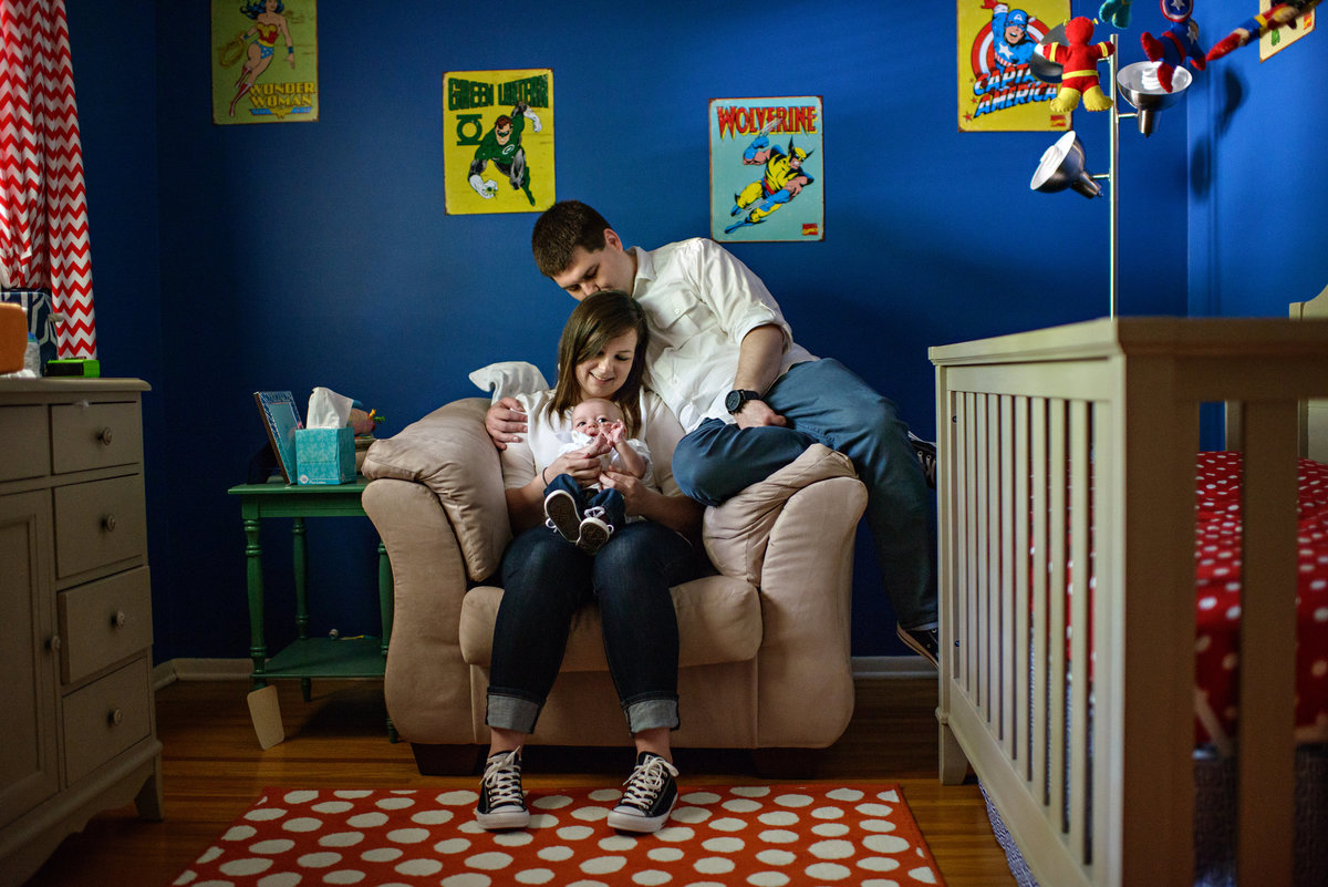 New parents hold their baby in the nursery filled with comic book characters.