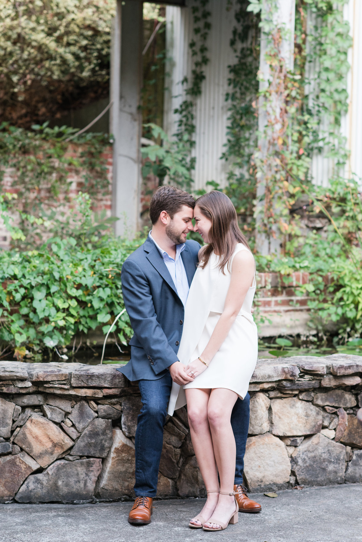 a bride wearing a short white dress sitting on her fiances leg who is wearing a navy suit sitting on a brick wall in front of greenery in Saxapahaw NC