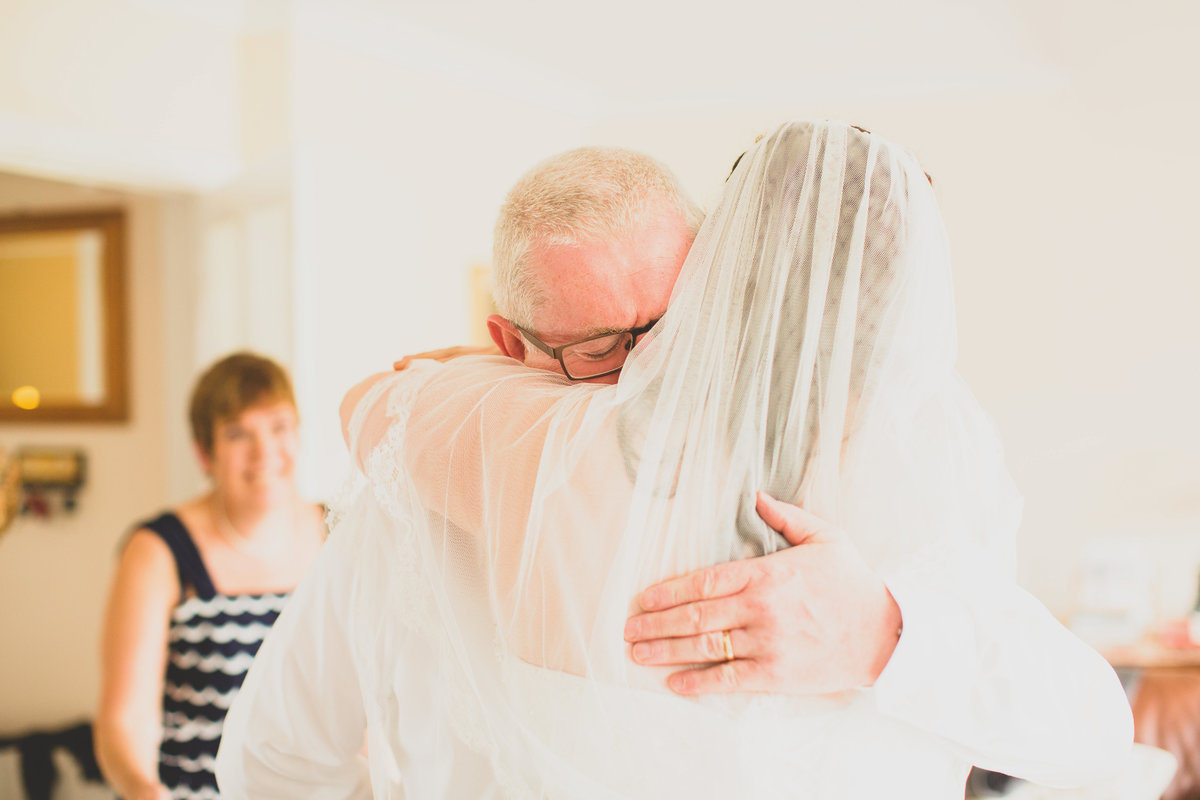 father hugging bride and crying after seeing her in wedding dress for first time