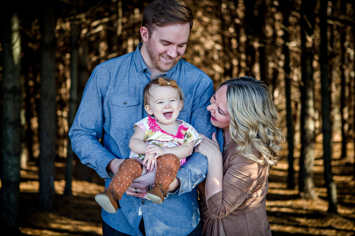 Family of three playing and laughing together in a forest of pine trees for their family pictures by Knoxville Wedding Photographer, Amanda May Photos.