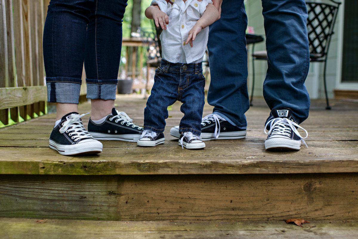 A family portrait of new parents and their baby in converse sneakers.