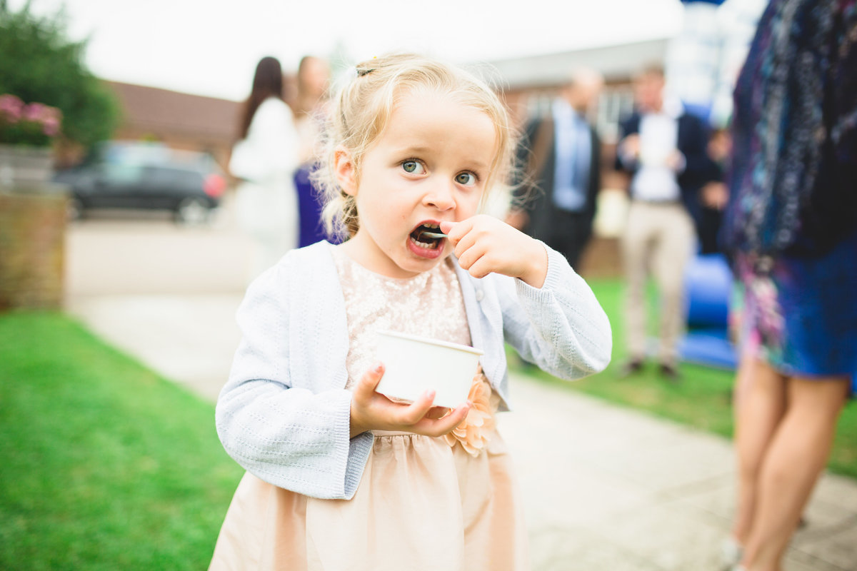 a girl is eating ice cream at a relaxed outdoor wedding