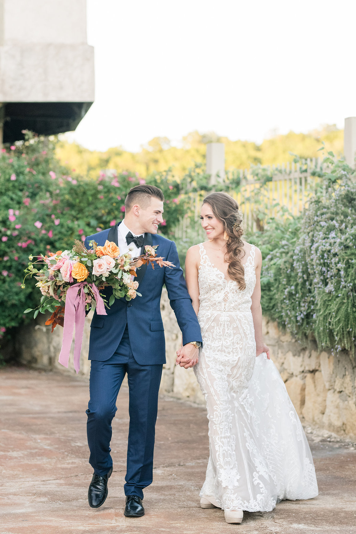 Villa Antonia Wedding Photographer captures couple leaving venue with fall bridal bouquet