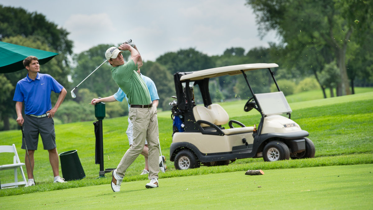 Man golfing at Jesuit high school fundraiser, Chicago, IL.