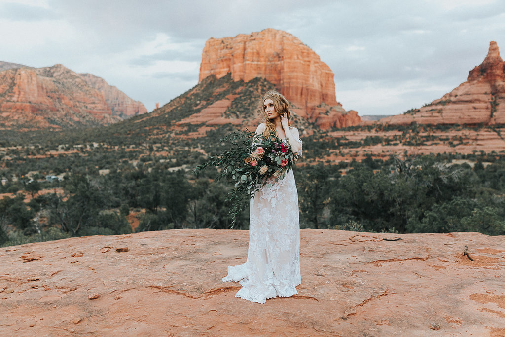 A portrait of a Boho bride in her Free People dress on the Red Rock cliffs in Sedona, Arizona.