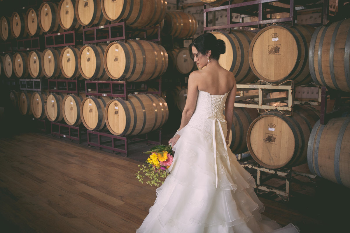 Austin Family Photographer, Tiffany Chapman, bride in front of wine barrels photo