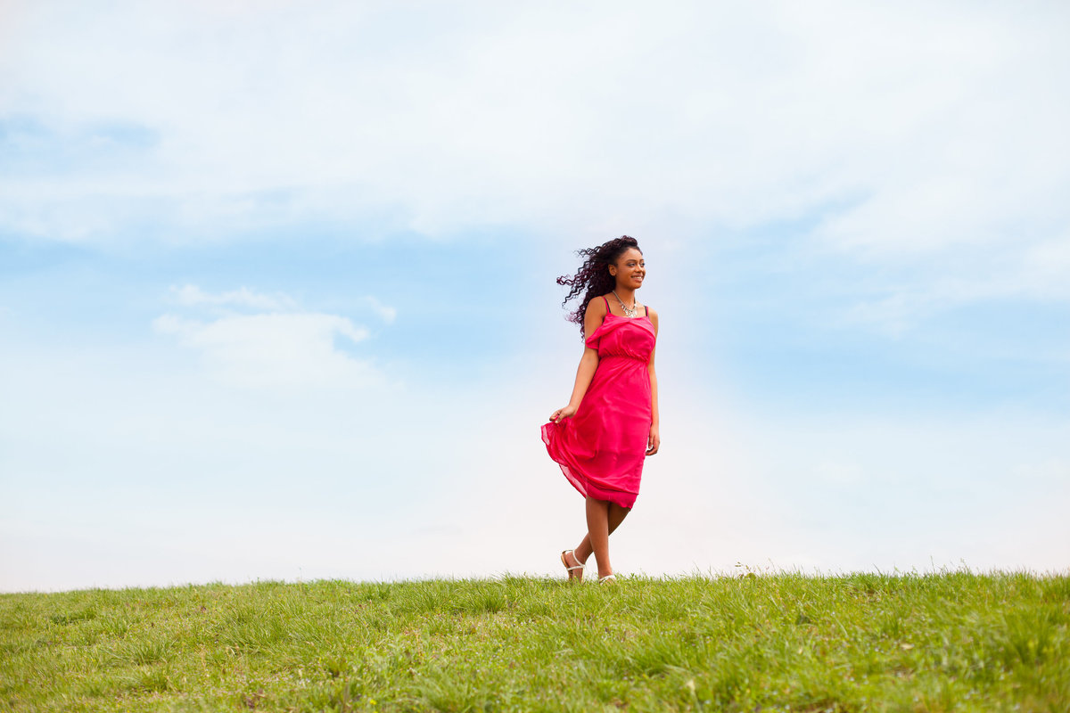 Senior Girl waking on hill in red dress