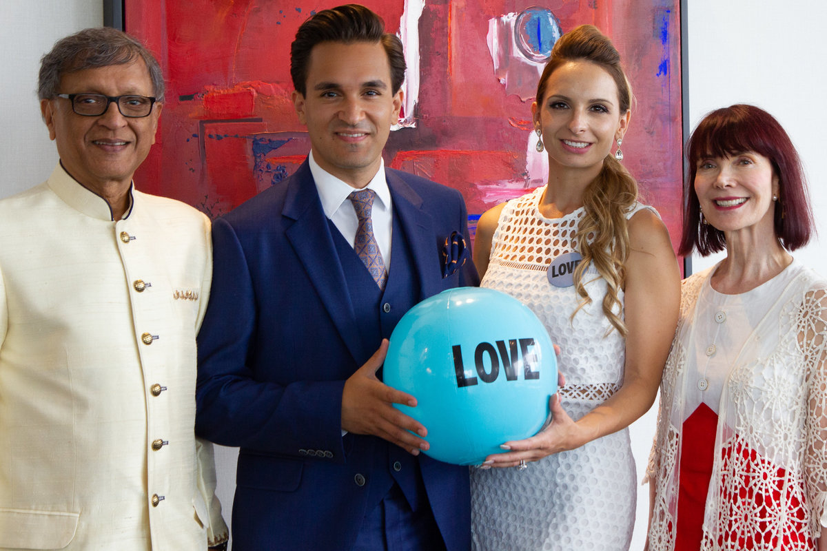 Newly weds with grooms parents holding a blue beach ball that says LOVE after their Toronto rooftop wedding ceremony