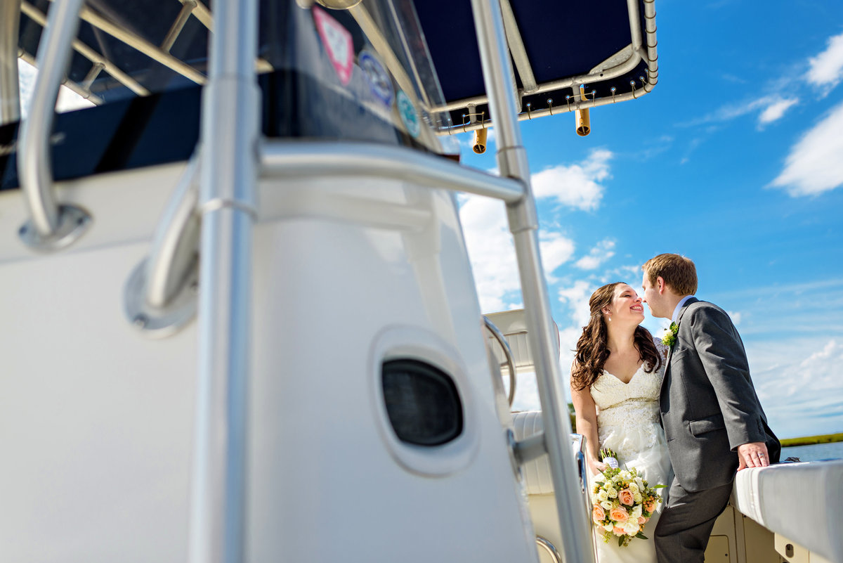 A bride leans in for a kiss from her groom on a yacht after their wedding on long beach island, NJ.