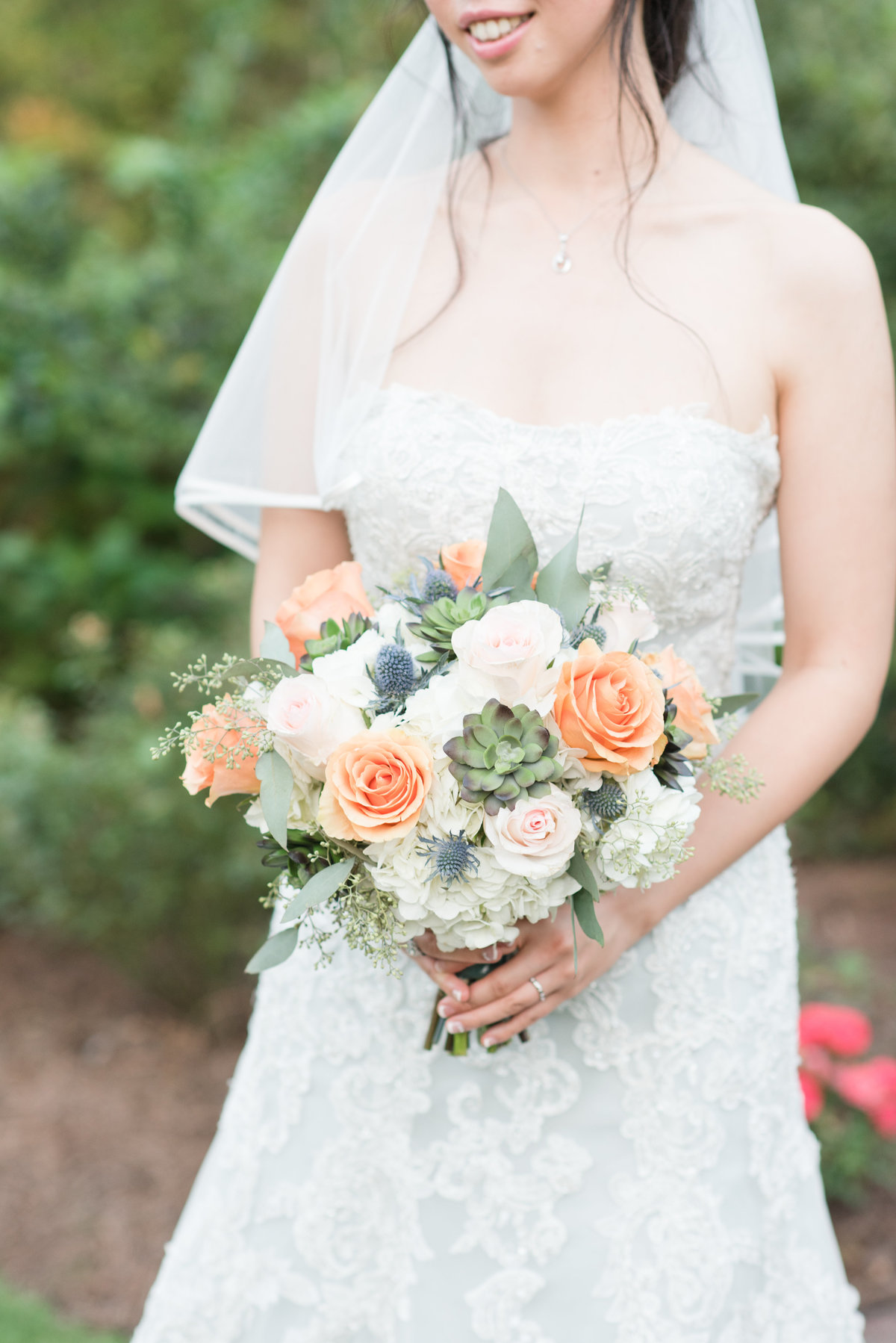 a bride wearing a strapless light blue wedding dress with mid-length veil holding white and orange wedding bouquet in front of an elegant little garden with the focus on the wedding bouquet  at Barclay Villa
