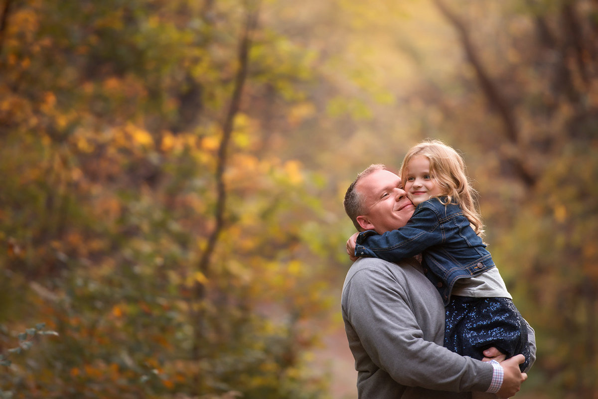 a little girl snuggles her dad in the woods during golden hour