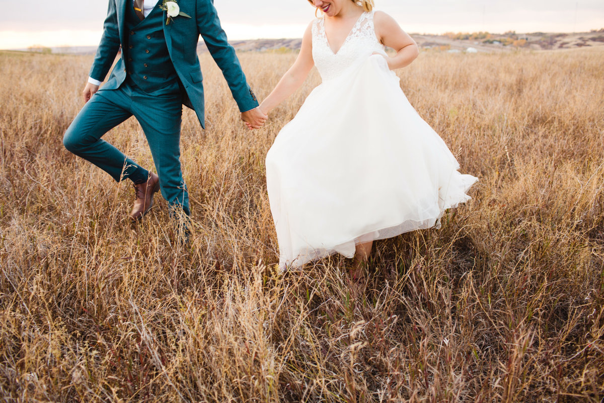 Groom's blue suit and modern bridal gown walking through tall grass