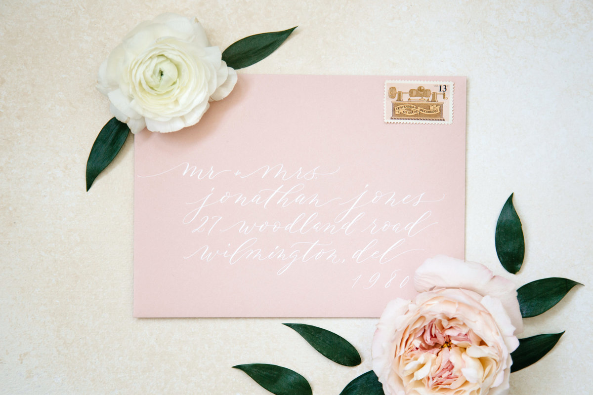 Custom calligraphy white ink on blush envelope