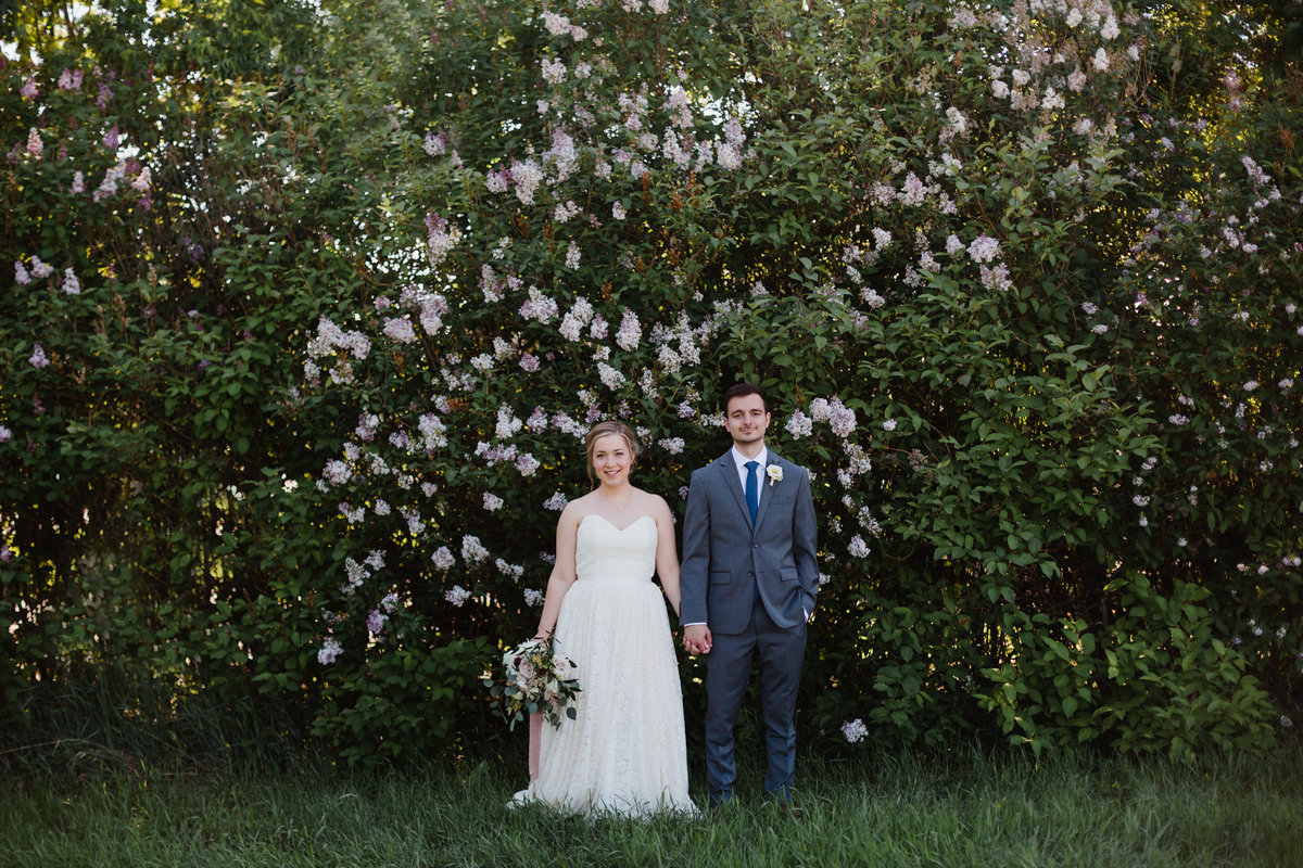 Modern wedding couple in front of lilac trees in Southey after there afternoon summer ceremony