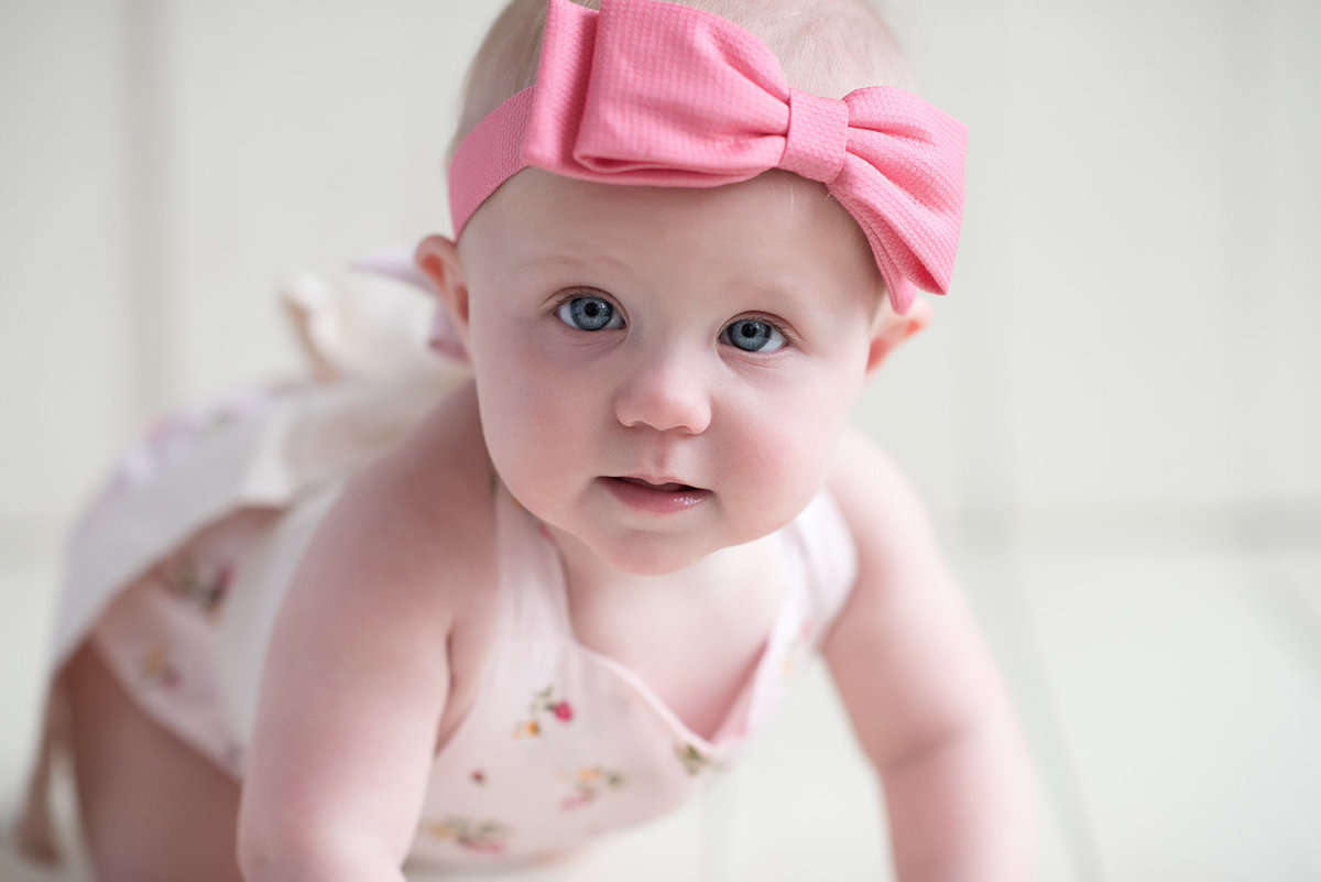a baby girl poses in a pink headband