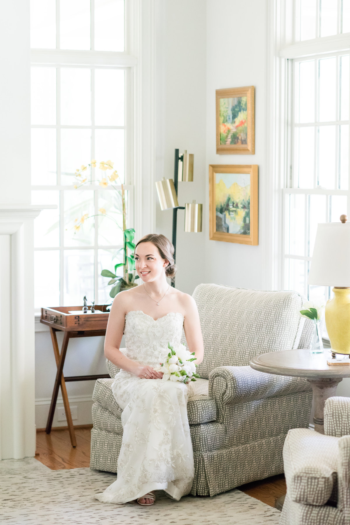 a bride wearing a laced strapless dress with no train sitting on a gray master seat in an elegant home looking off holding a white and green wedding bouquet