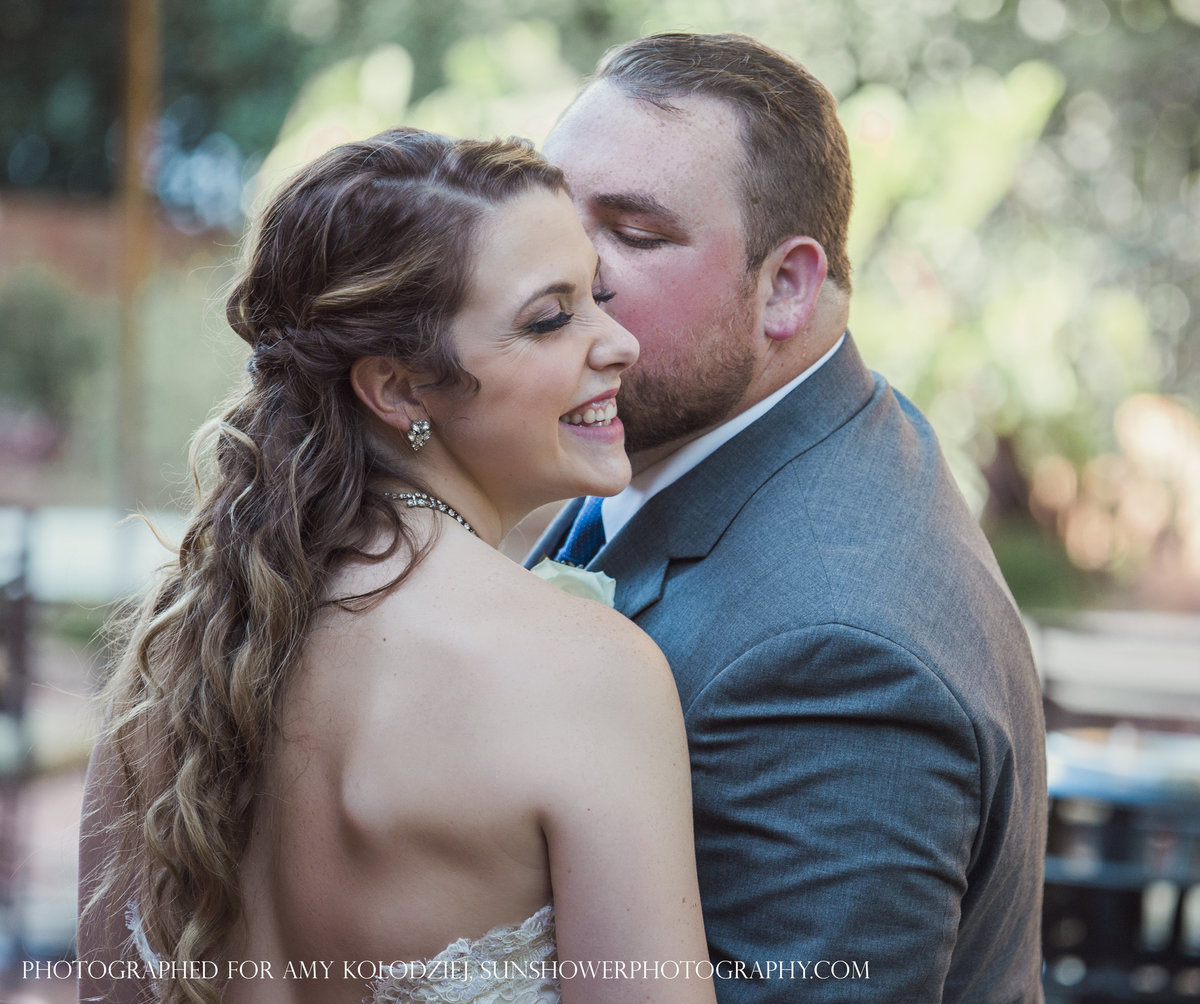 charlotte wedding photographer jamie lucido captures a fun moment with the bride smiling and groom kissing her