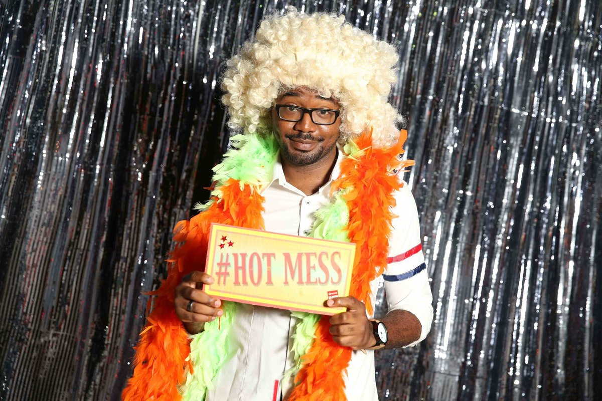 Man poses with sign while wearing a multitude of photobooth props. Photobooth by Ross Photography, Trinidad, W.I..