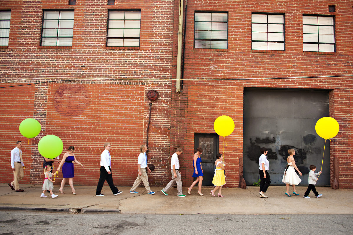 A wedding party march down the street with large balloons.