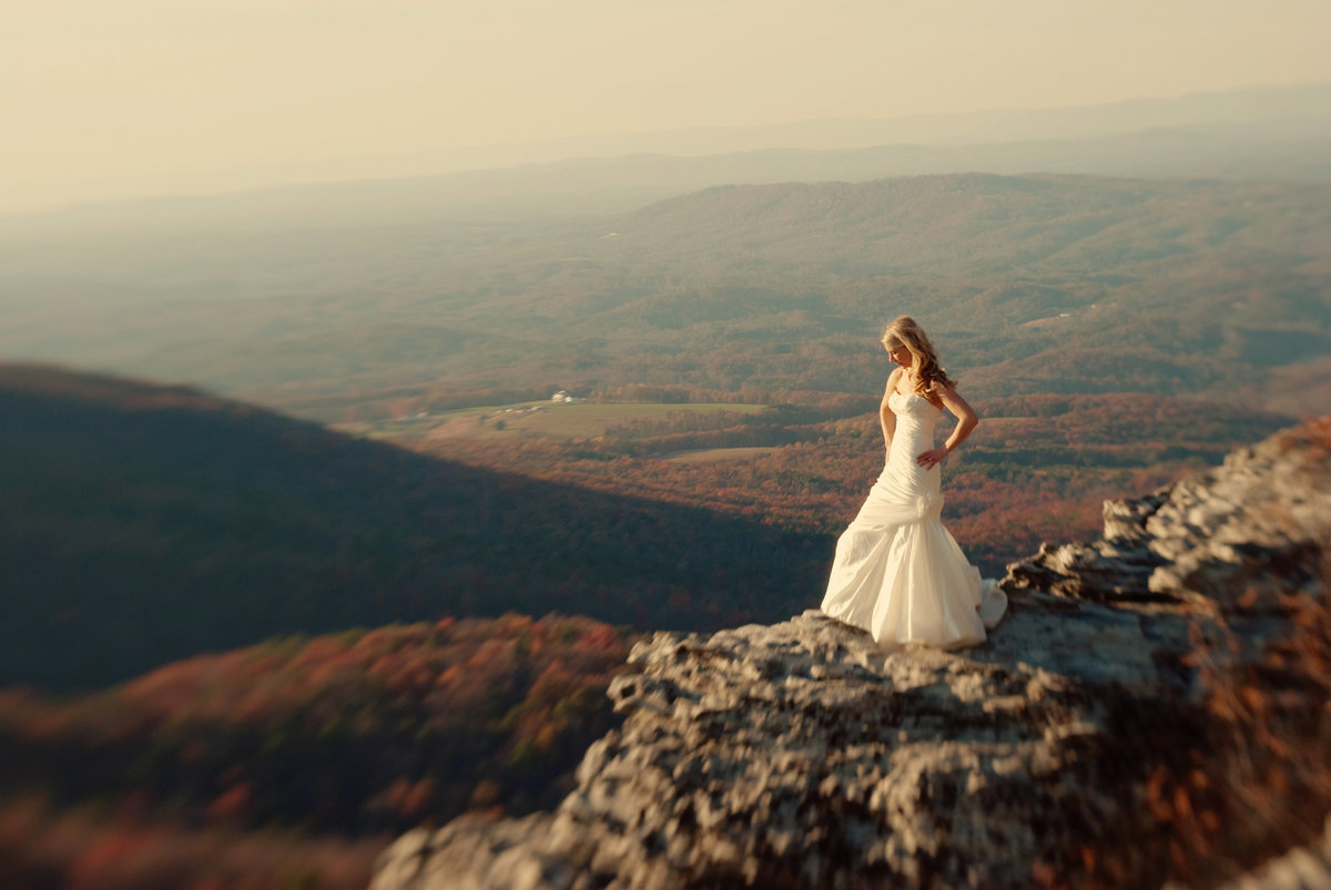 a bride stands on edge of hanging rock in nc