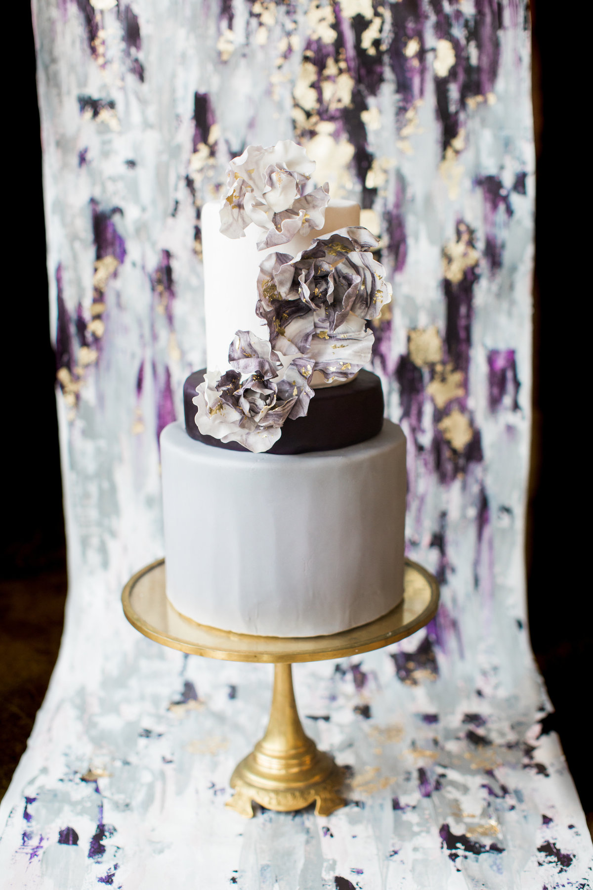 Cake in front of custom abstract gold and purple wedding backdrop By Brittany Branson