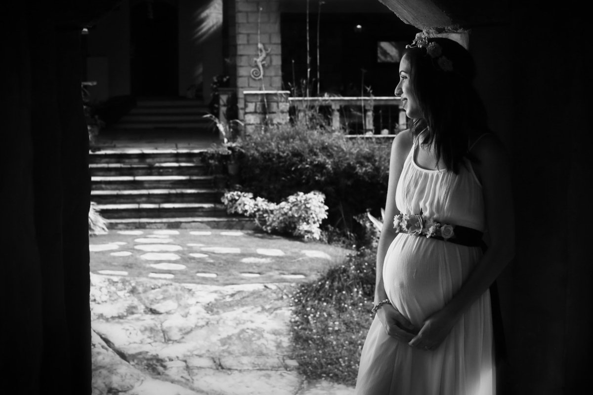 B+W maternity shot of mom in a doorway to a landscaped garden. Photo by Ross Photography, Trinidad, W.I..