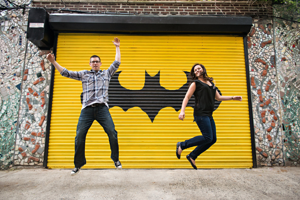 Engaged couple jump in front of a graffitied door on south street in philly.