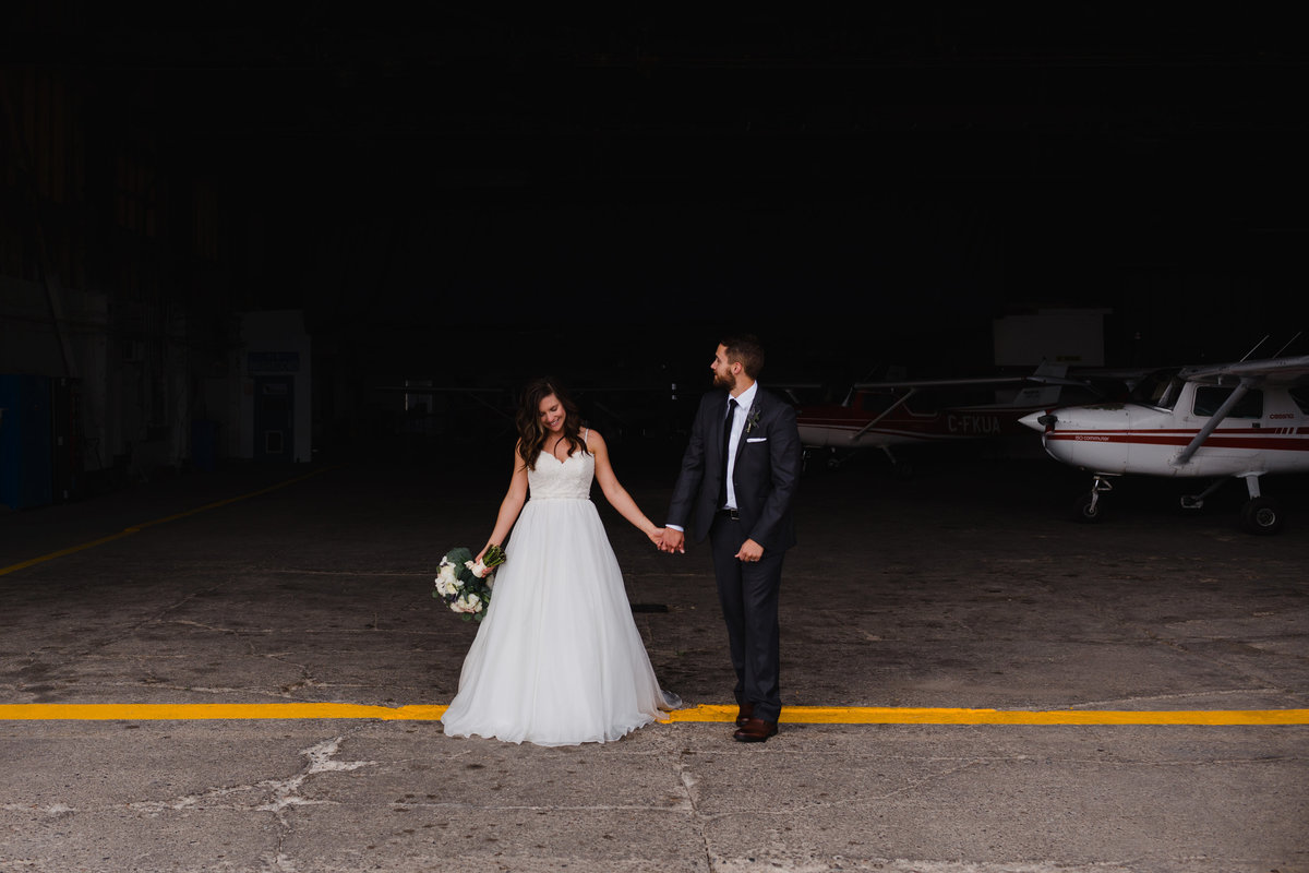 Airplane Hanger wedding photos in Regina. Couple who loves to travel.