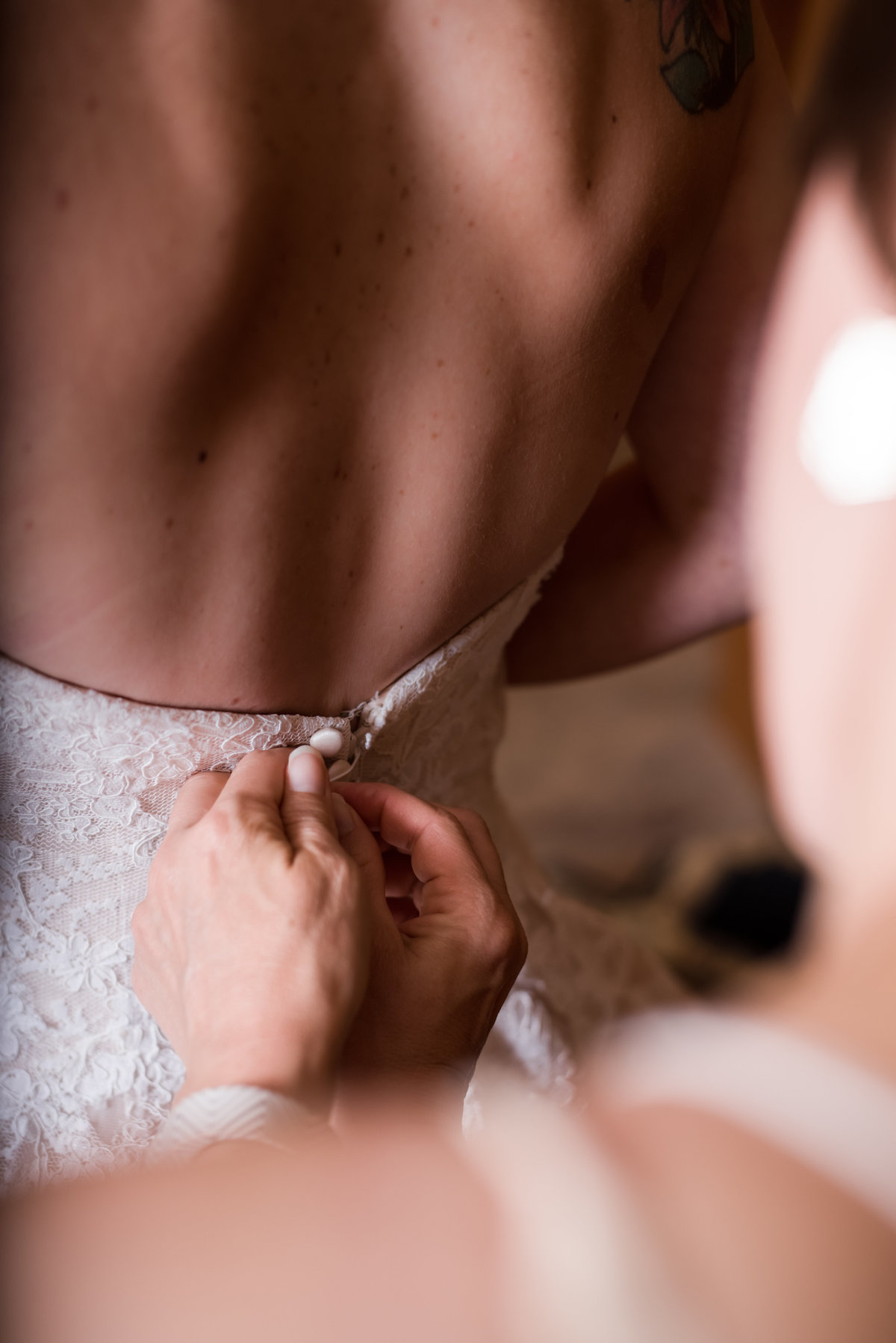 Bride and her final touches as she puts on her Morilee Wedding gown