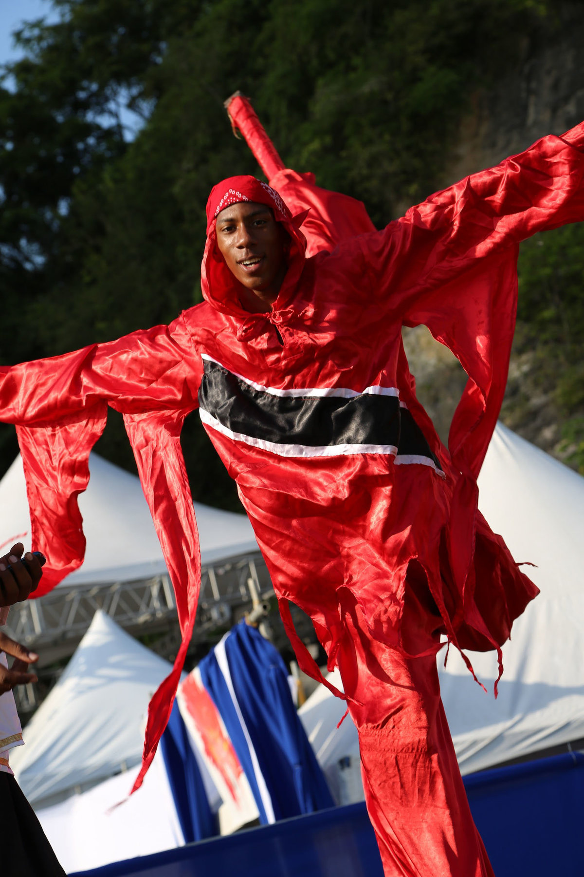 A traditional Trinidadian moko jumbie (stilt walker) performs a trick while dancing in patriotic costume. Photo by Ross Photography, Trinidad, W.I..