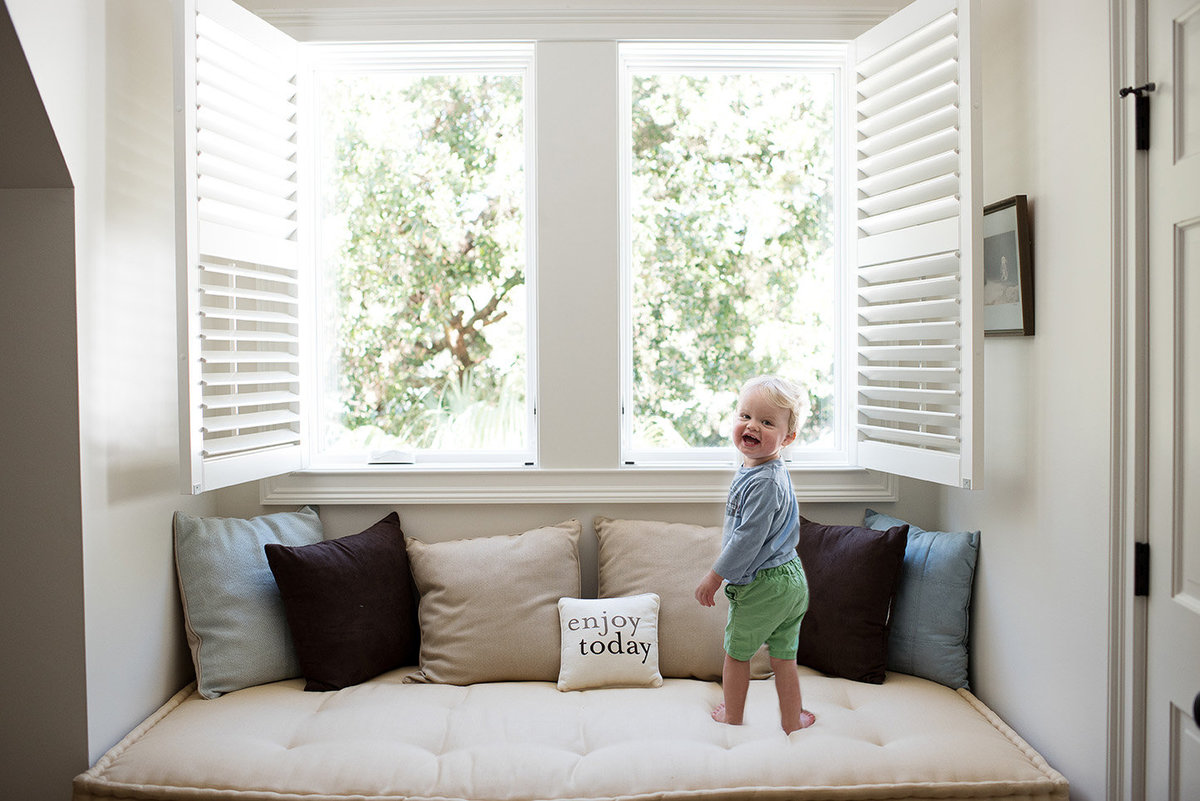 a toddler boy in a bay window smiling at the camera