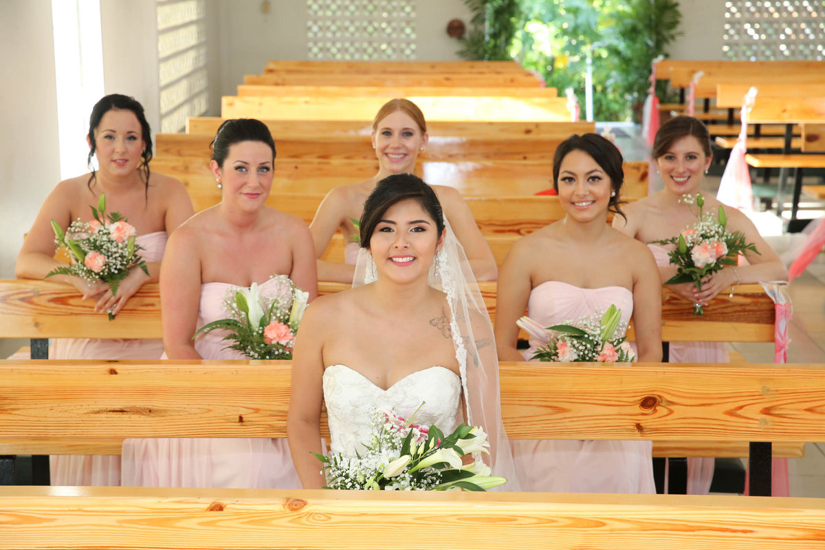 Bride with bridal party sitting in church pews. Photo by Ross Photography, Trinidad, W.I..
