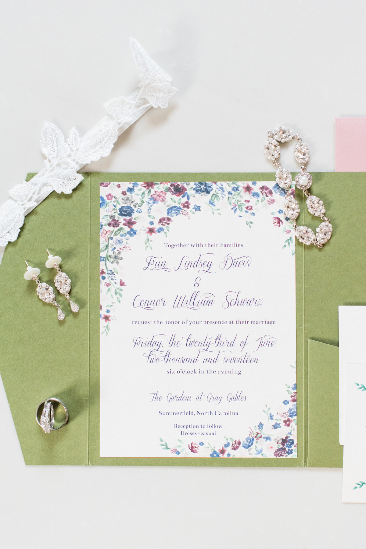 a colorful folded invitation suite surrounded by vintage jewelry on white marble table