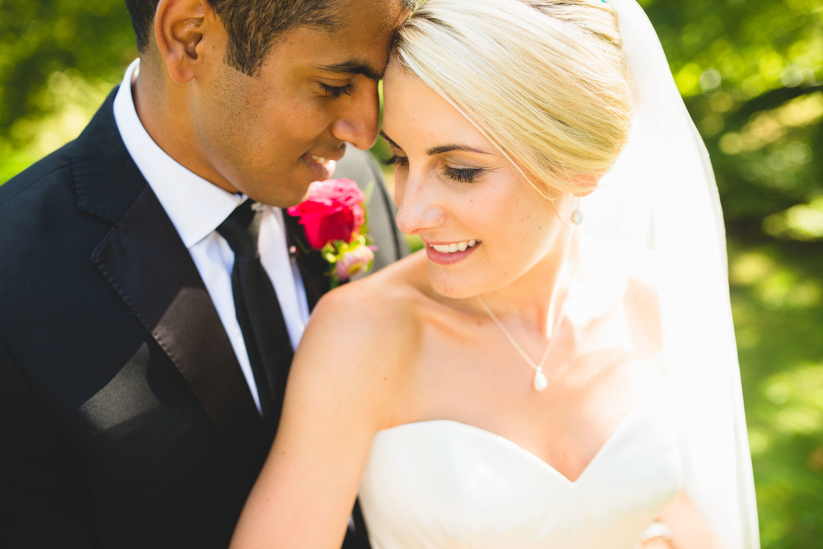 closeup photo of bride and groom in black suit with red rose
