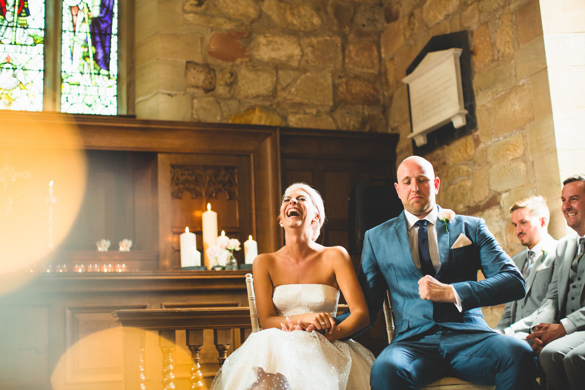 fun photograph of bride and groom laughing during the wedding ceremony in a small chapel