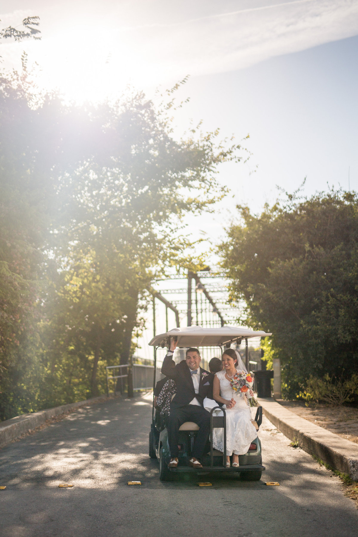 bride and groom sitting on golf cart after wedding ceremony heading to take pictures on bridge