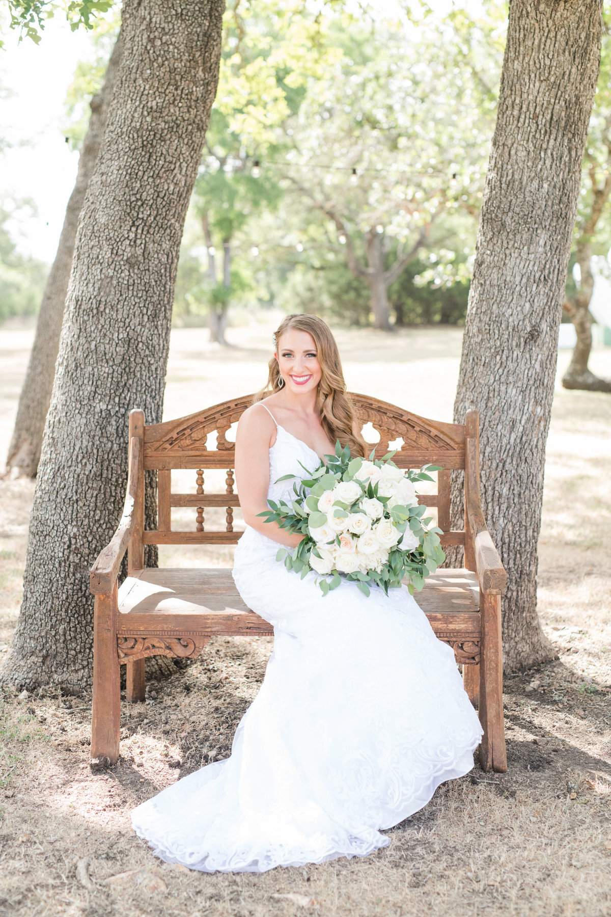 Bride sits on Bench for bridal portraits at Kindred Oaks holding a white and green bouquet