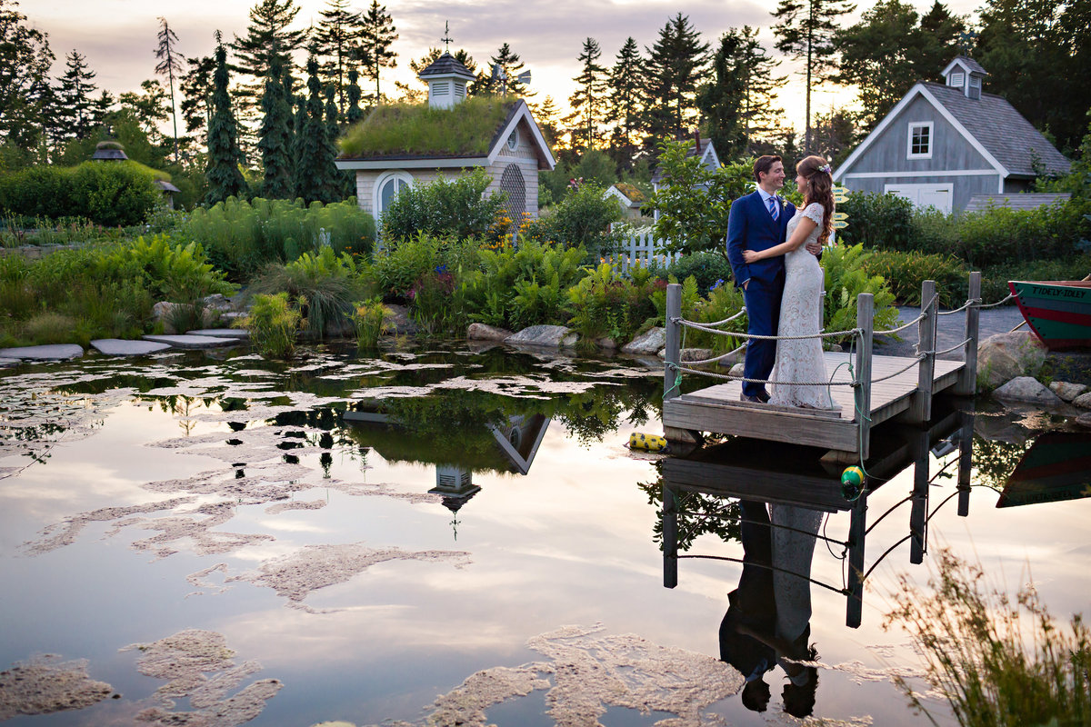 Boothbay Harbor Maine Wedding Photographer Botanical Garden couple standing on the water with the plants and flowers as the backdrop to this sunset photo of the bride and groom