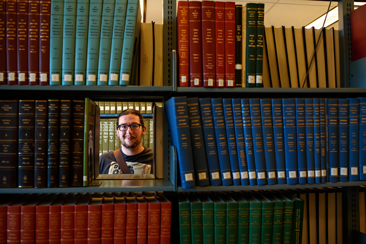 Portrait of a college student in a library framed by books.