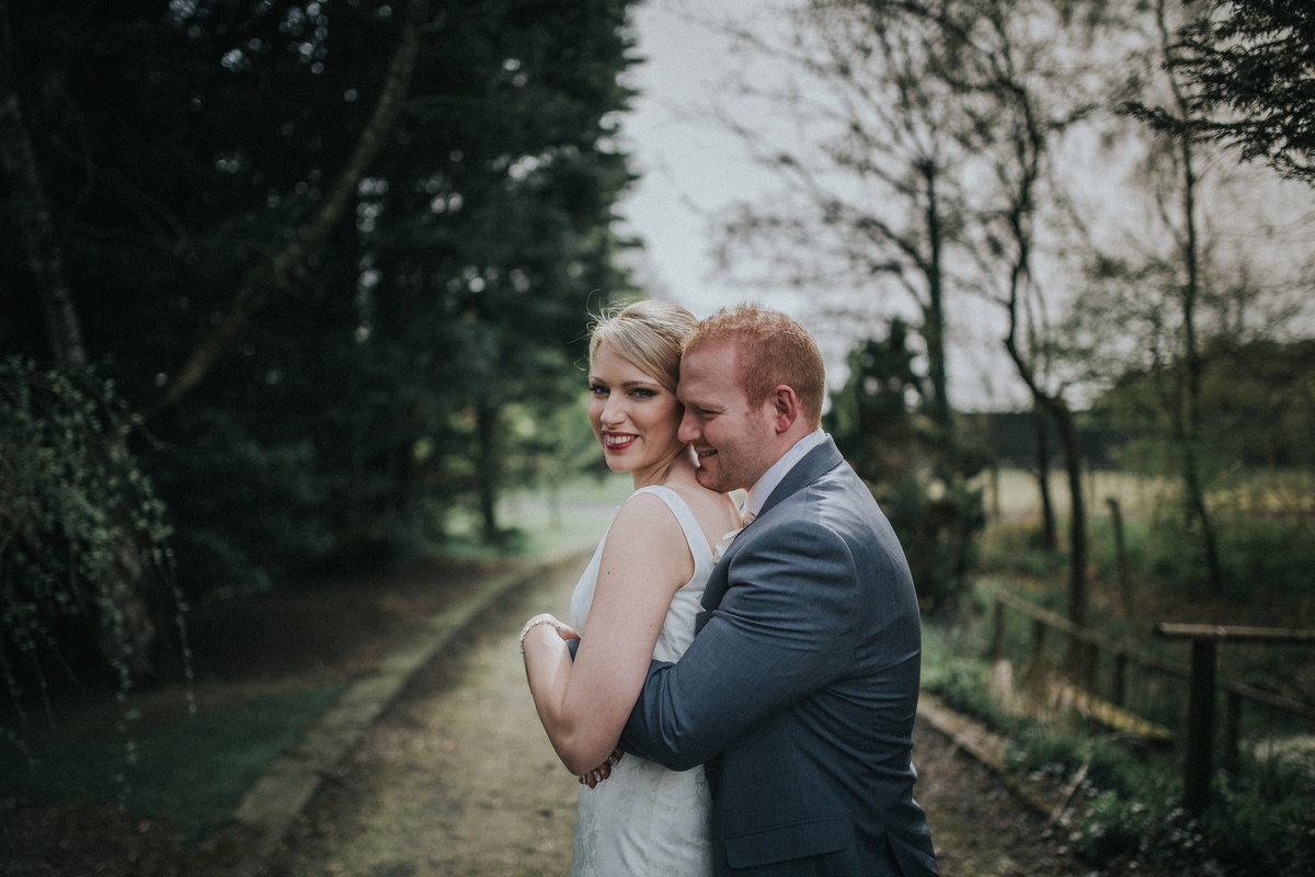 Groom hugging his new wife as she smiles at camera - Lancashire Wedding Photographer Jono Symonds