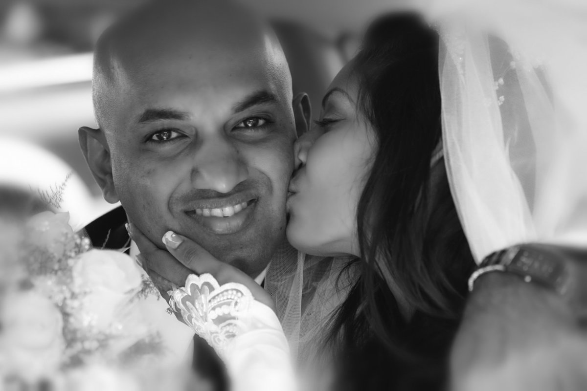 B+W of bride kissing groom's cheek . Photo by Ross Photography, Trinidad, W.I..