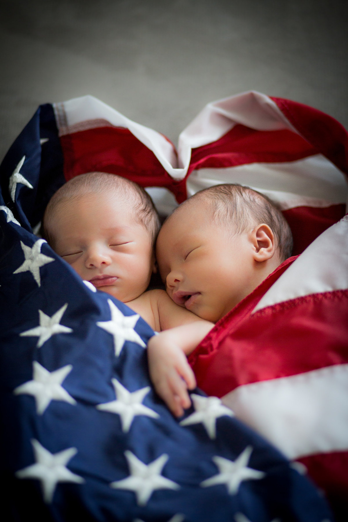 Newborn twins photography session of two infants wrapped in the American flag.