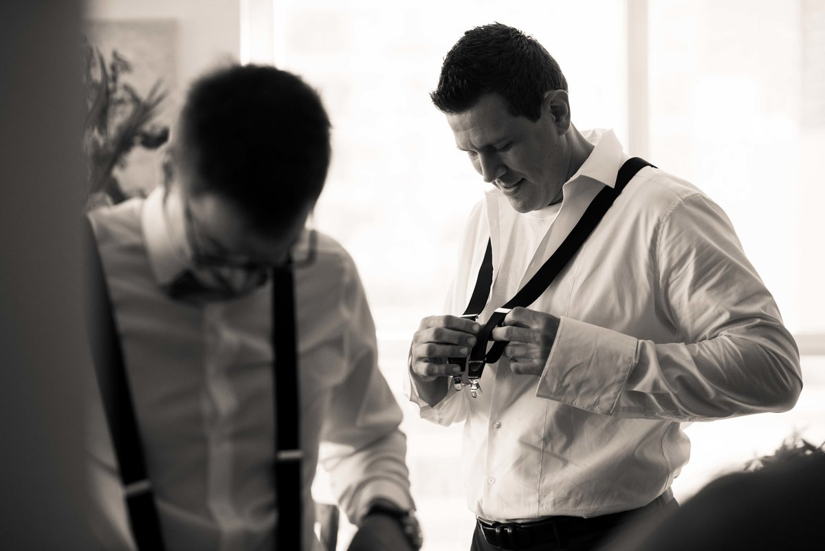 Groom puts on his suspenders, Chicago wedding.