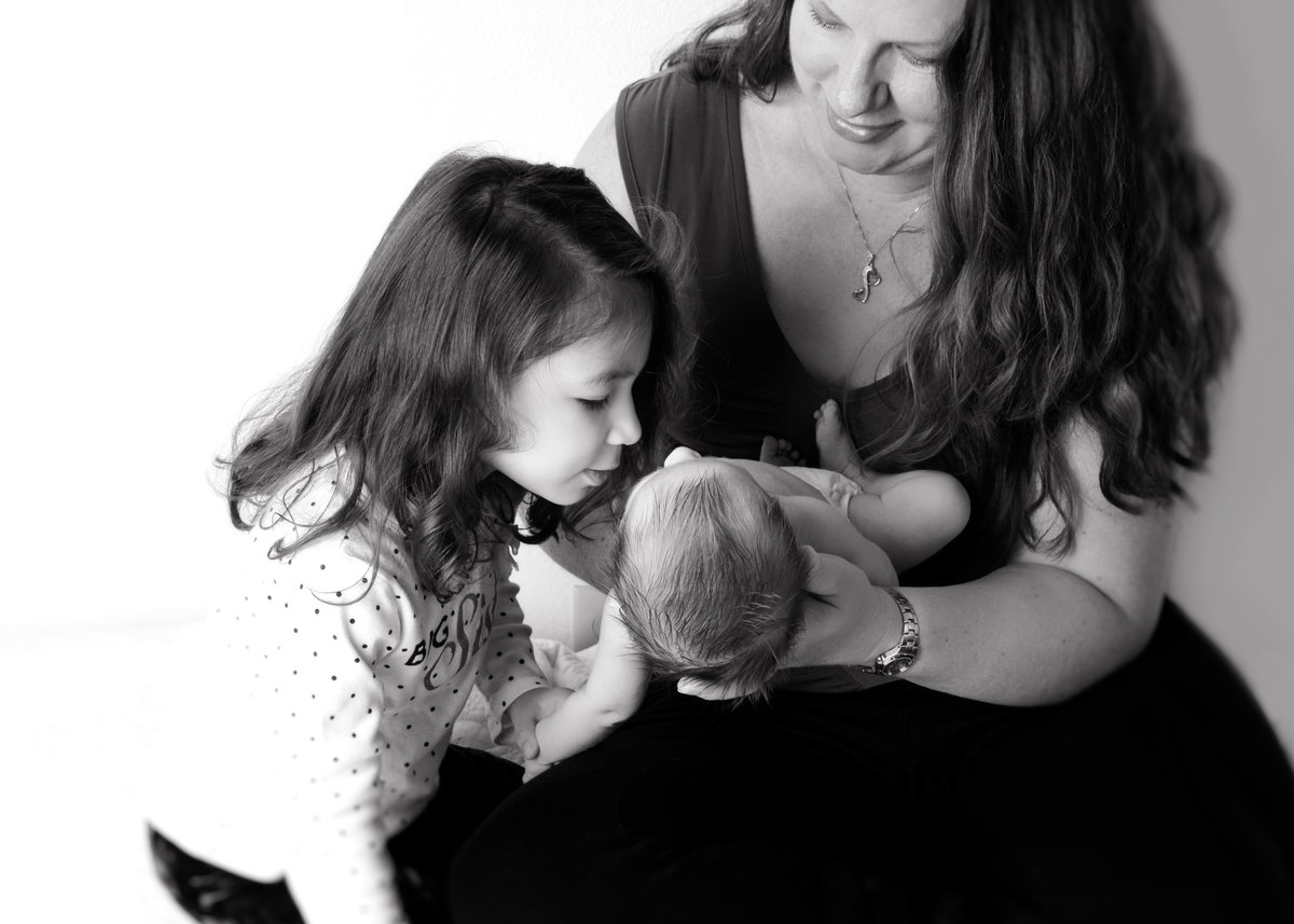 black and white photo of mom, big sister and baby brother being held as big sis is leaning over softly to kiss hime