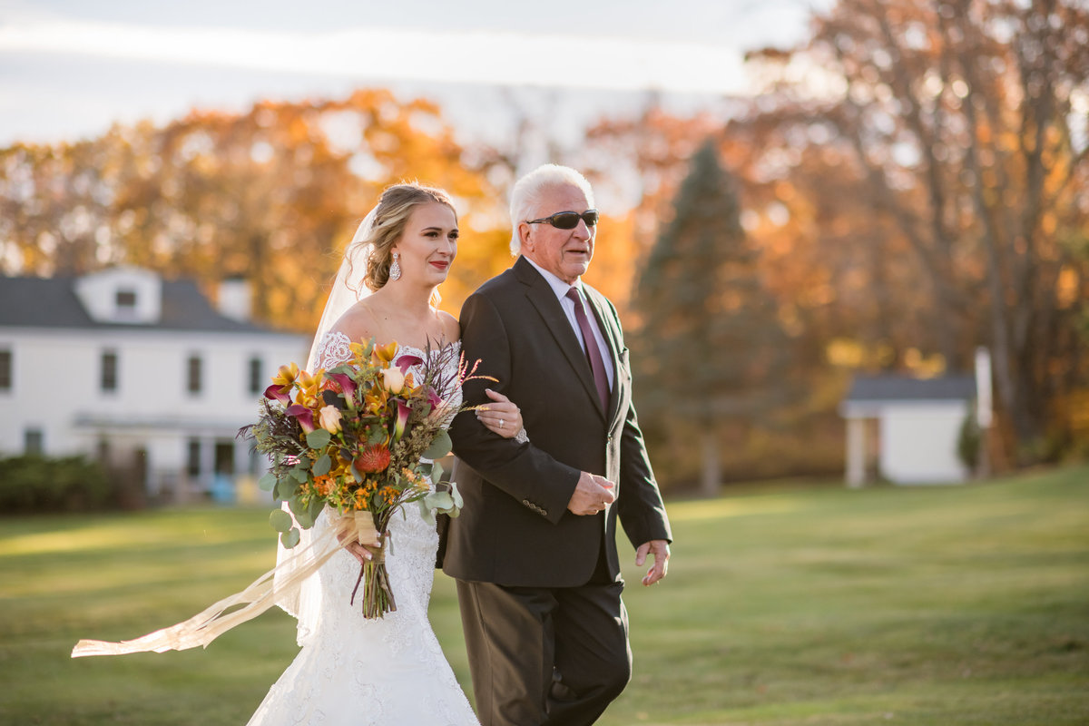 bride and father walking down the aisle with autumn leaves in background