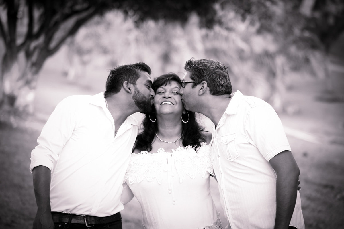 Family portrait in B+W with son and father sandwiching mom while kissing her on her cheeks. Photo by Ross Photography, Trinidad, W.I..