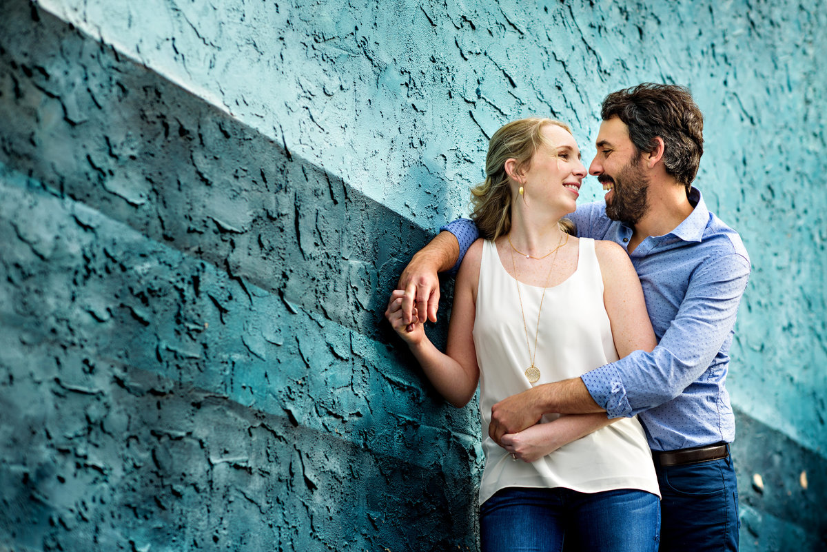 A man holds his fiance while they lean in front of a blue wall on south street.