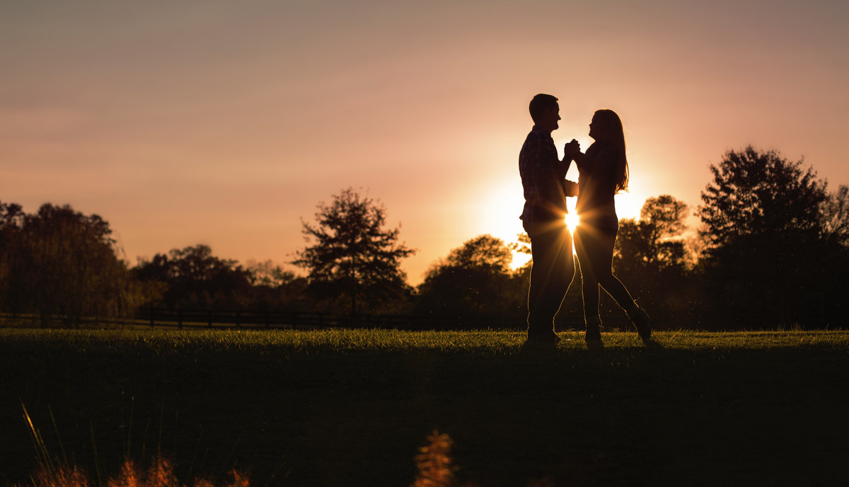 A couple shares a moment at sunset silhouette at Morning Glory Farm in  Charlotte NC during their engagement session